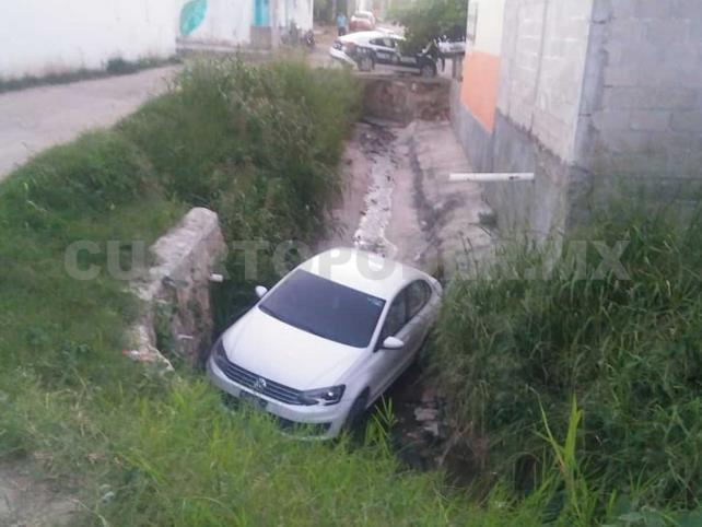 Automóvil se echa de reversa y cae en canal