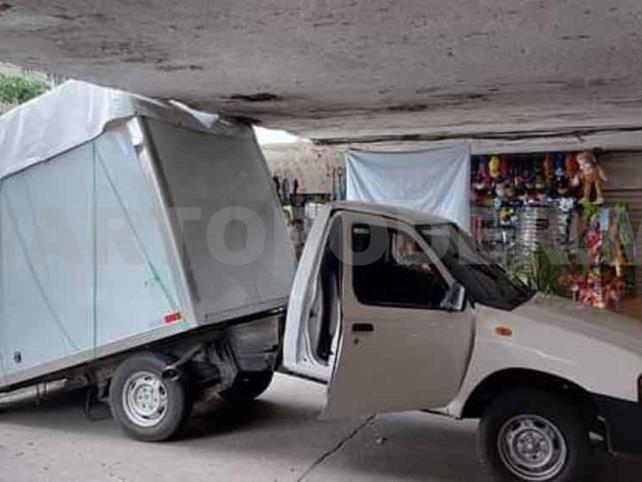 Vehículo queda atascado al chocar con paso a desnivel